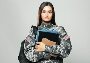Veteran wearing backpack and holding notebooks for education